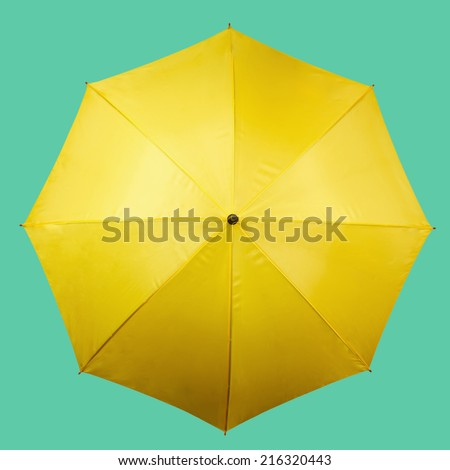 Yellow umbrella on a light blue background - stock photo