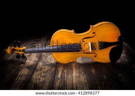 Yellow violin on dark wooden background - stock photo
