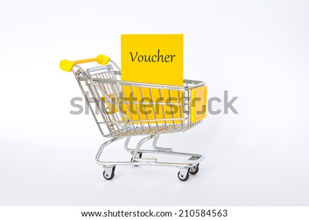 Yellow voucher in shopping trolley in front of white, copy space - stock photo