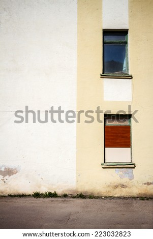 Yellow wall of a abandoned house with two windows - stock photo