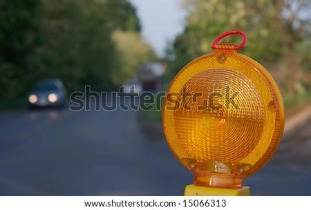 Yellow warning light at a road construction - stock photo