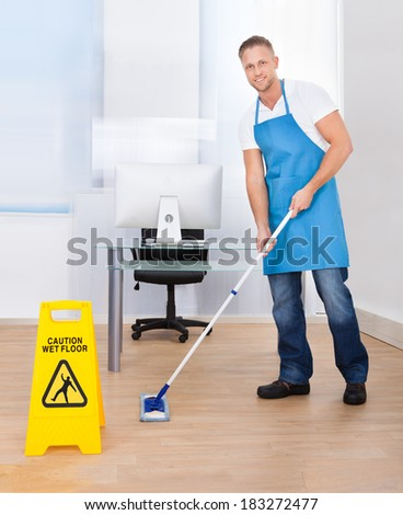 Yellow warning notice to caution people to a slippery wet surface as a janitor mops the floor in an office building - stock photo