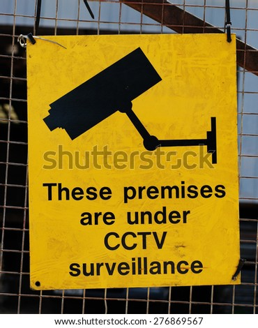Yellow warning sign for CCTV surveillance using security cameras to secure a premises against crime on a wire mesh fence - stock photo