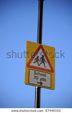 Yellow warning sign for school crossing - stock photo