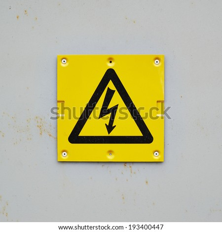 Yellow warning sign on a gray wall composition - stock photo