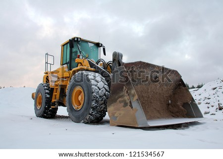 Yellow wheel loader at sand pit in winter snow. - stock photo