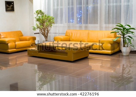 Yellow wide leather sofa, armchair and coffee table in hall interior. The picture on the wall is by the photographer and was inserted here with a graphic program. - stock photo