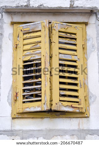 Yellow window with shutters in old stone house, Croatia - stock photo