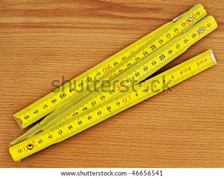 yellow wooden meter over the wooden background - stock photo