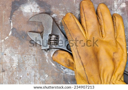 Yellow working glove and spanner lying on old worn workbench surface. - stock photo