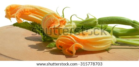 Yellow zucchini blossoms, leaves and tendril on wooden cutting board - stock photo