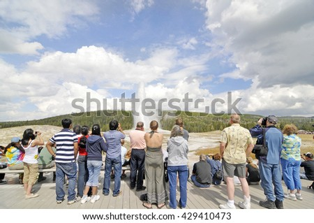YELLOWSTONE NATIONAL PARK, WYOMING - SEPTEMBER 6: Tourists photographing Old Faithful Geyser in Yellowstone National Park on September 6, 2009.  - stock photo