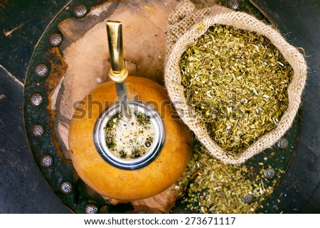 Yerba mate in a traditional calabash gourd and bag of dry herb - stock photo