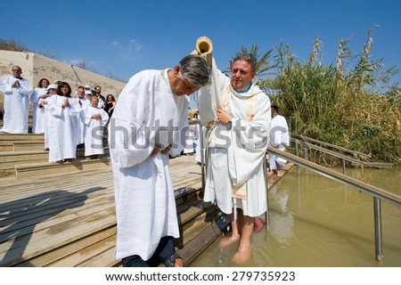 YERICHO, ISRAEL - OCT 15, 2014: A man is being baptized by water during a baptism ritual at Qasr el Yahud near Yericho on the Jordan river - stock photo