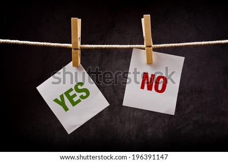 Yes and No concept, words printed on note paper and attached to rope with pins. Concept of choice, options, decision making or dilemma. - stock photo