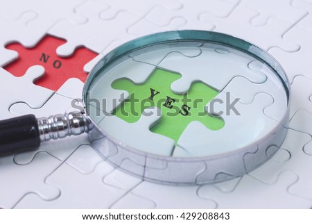 YES and NO puzzle with magnifier glass - stock photo