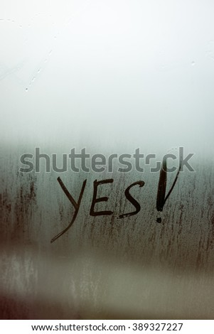 Yes written on foggy window background. Positive agreement sign texture - stock photo