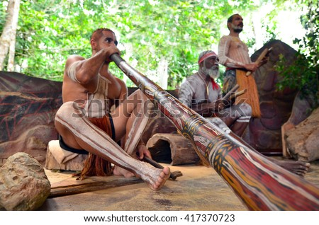 Yirrganydji Aboriginal men play Aboriginal music on didgeridoo and wooden instrument during Aboriginal culture show in Queensland, Australia. - stock photo