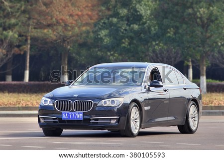 YIWU-CHINA-JAN. 26, 2016. BMW 5 series L on the road. BMW sales will be hit in 2016 by cut-throat competition, slowing Chinese economy and government crackdown on graft and conspicuous consumption.  - stock photo