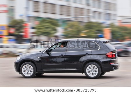 YIWU-CHINA-JAN. 15, 2016. BMW X5 3.5i on the road. BMW sales will be hit in 2016 by cut-throat competition, slowing Chinese economy and the government crackdown on graft and conspicuous consumption. - stock photo