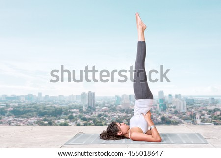 Yoga and meditation in a modern city. Young woman doing yoga on the roof - stock photo
