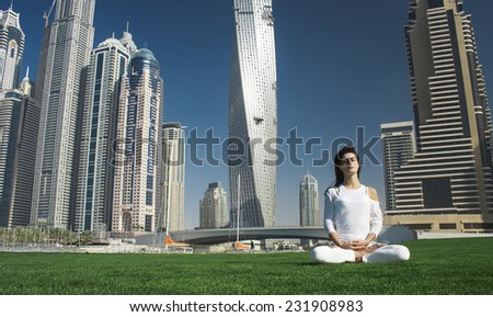 Yoga and meditation in a modern urbanistic city. Young attractive girl - yoga meditates against huge modern skyscrapers of Dubai.  - stock photo