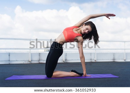 Yoga and meditation in a modern urbanistic city. Young attractive girl - yoga meditates against modern skyscrapers - stock photo