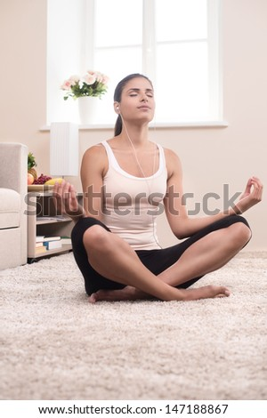 Yoga at home. Beautiful young women meditating at home while sitting in a lotus position - stock photo