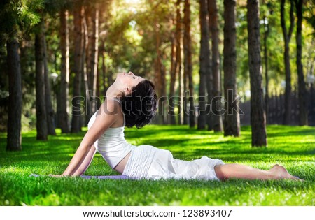 Yoga bhujangasana cobra pose by woman in white costume on green grass in the park around pine trees - stock photo