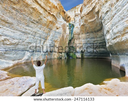 "Yoga classes in the gorge Ein-Avdat, Israel. Woman in white performs asana ""Sun salutation"" - stock photo"