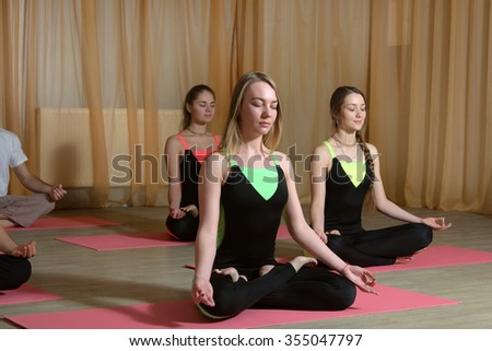 Yoga classes. Three girls in identical costumes perform meditation exercises on mats on the wooden floor - stock photo