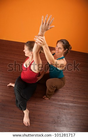 Yoga coach helping student stretch shoulders - stock photo
