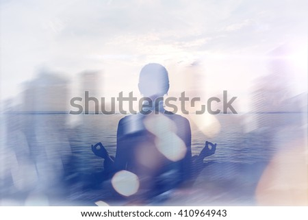 Yoga concept. Double exposure. Woman doing yoga practice on the beach and silhouette of modern city. Blurred effect, lens flare effect, intentional sun glare - stock photo