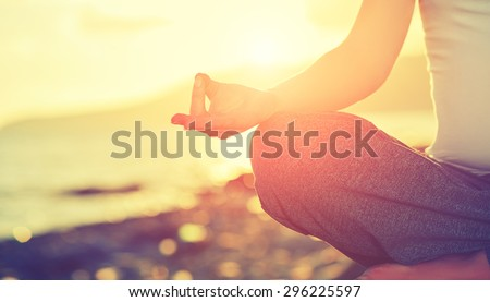 Yoga concept. hand woman practicing lotus pose on the beach at sunset - stock photo