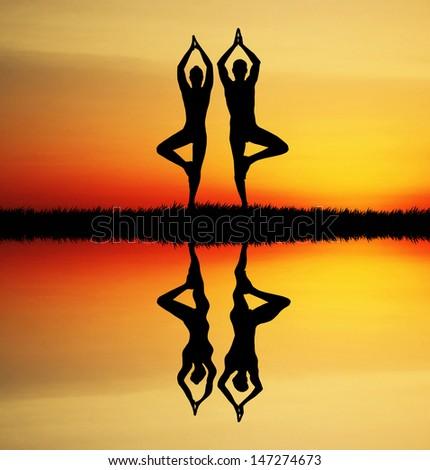 Yoga couple at sunset - stock photo