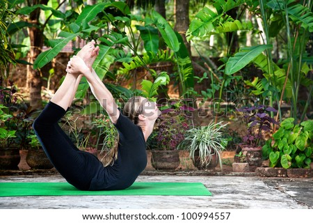 Yoga Dhanurasana bow pose by woman in black cloth in the garden with palms, banana trees and plants in the pots - stock photo