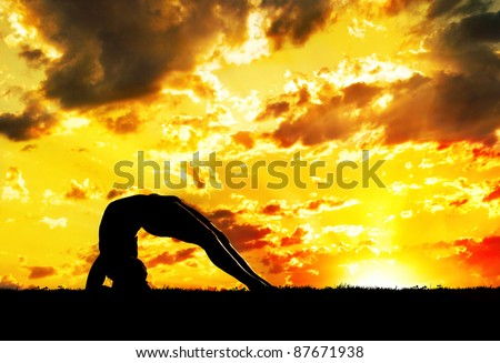 Yoga Dwi Pada Viparita Dandasana Upward Facing Two-Foot Staff Pose inverse pose by Man in silhouette with orange sunset sky background. Free space for text - stock photo