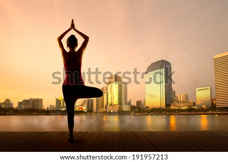 Yoga exercises at the city park - stock photo