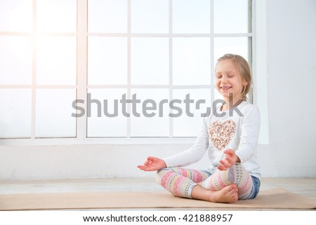 Yoga for children - concept. Little girl sitting in a yoga pose. Girl do yoga indoors. Child girl exercising yoga in gym near the window. - stock photo