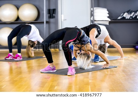 Yoga group stands in bridge at the fitness gym - stock photo