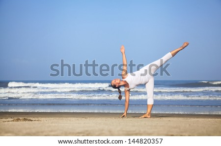 Yoga half-moon pose by woman in white costume on the beach near the ocean in India - stock photo