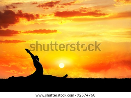 Yoga hanumanasana monkey pose by man silhouette at sunset sky background. Free space for text and can be used as template for web-site - stock photo