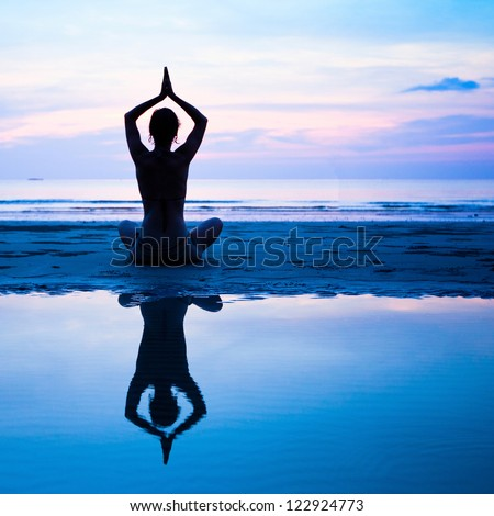 Yoga, harmony of health - silhouette young woman on the beach at sunset. - stock photo