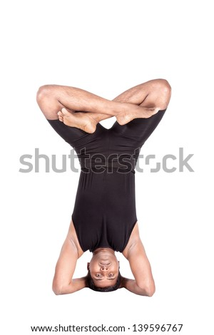 Yoga headstand pose in padmasana by Indian man in black costume isolated at white background. Free space for text - stock photo