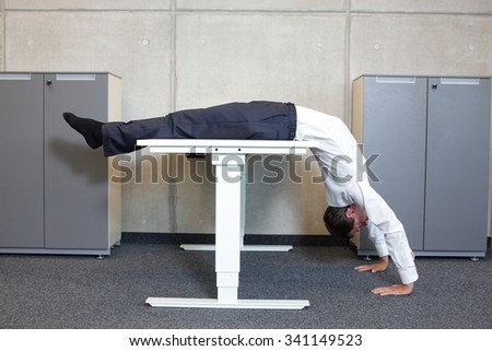 yoga in office. business man exercising at workplace - stock photo