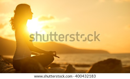yoga in the beach. woman meditating in lotus pose at sunset - stock photo