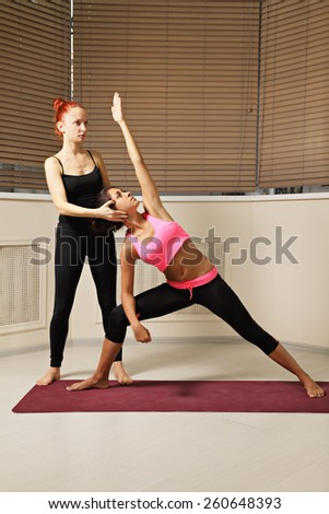 Yoga instructor helping brunette to keep head in line - stock photo