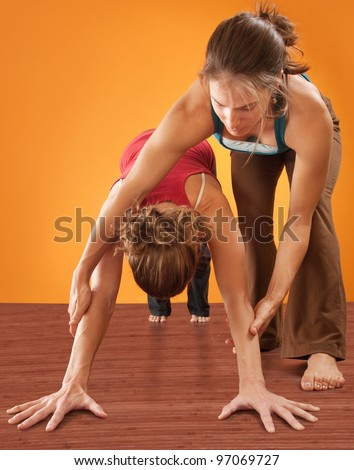 Yoga instructor helping student perform Adho Mukha Svanasana posture over orange background - stock photo
