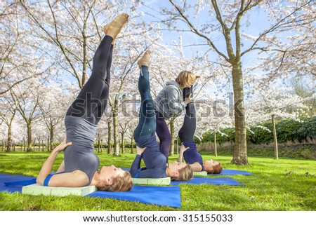Yoga instructor helping young women with shoulder stand (salamba sarvangasana) in a blooming spring park - stock photo
