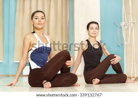 Yoga is a good stretching. Cheerful young women doing yoga together - stock photo